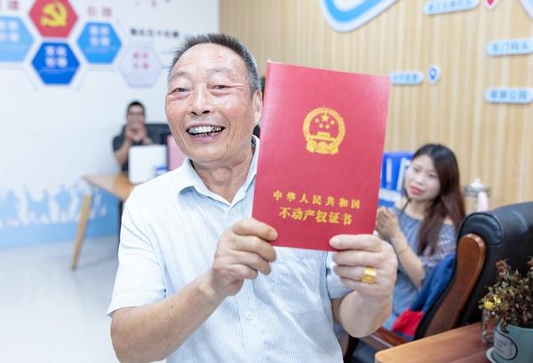 2021年7月9日,广安市广安区北辰街道香江国际小区居民高兴地展示自己刚领取到的房产证。.jpg
